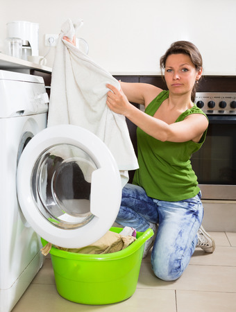 unsatisfactory: Tired young woman in jeans doing laundry with washing machine at home kitchen