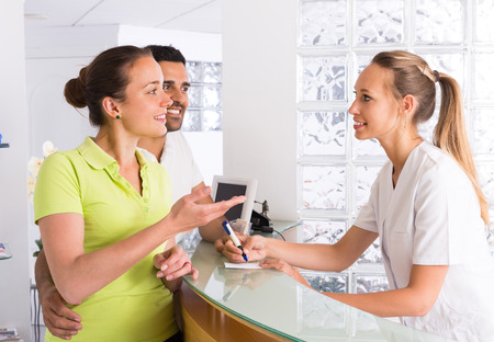 Young couple talking with secretary at reception in the clinic photo