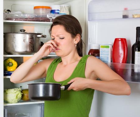oler: Muchacha que sostiene la nariz a causa del mal olor de los alimentos cerca de nevera en casa