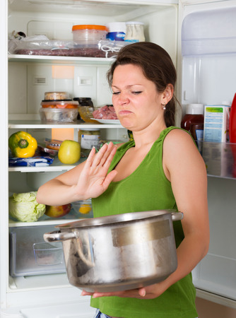 frowy: Woman holding her nose because of bad smell from food near refrigerator  at home