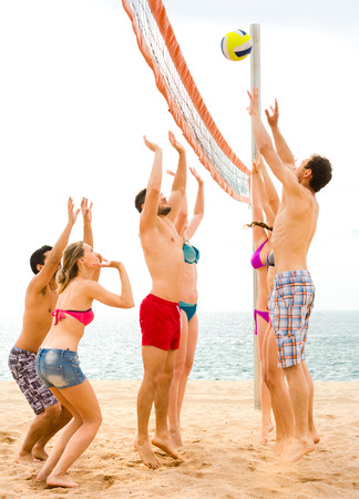 Sportive adults playing volleyball on a beach during summer vacation photo