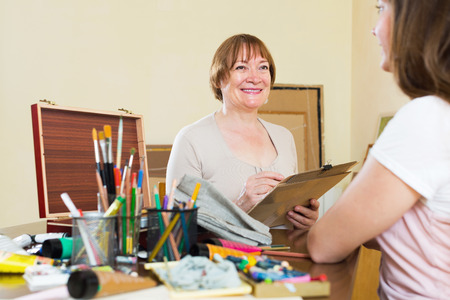 contentedness: Happy mature artist in the process of creating a new picture