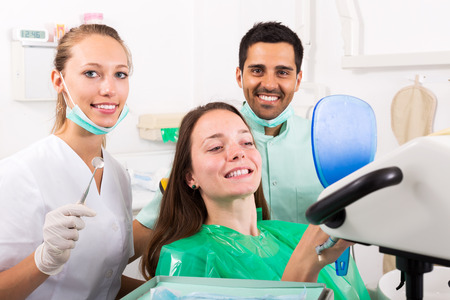 trained nurse: Smiling woman patient checks the result of the work of the dentist Stock Photo