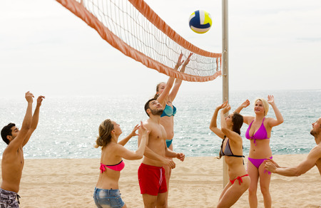 freetime activity: Smiling young group of friends having fun at beach and playing ball