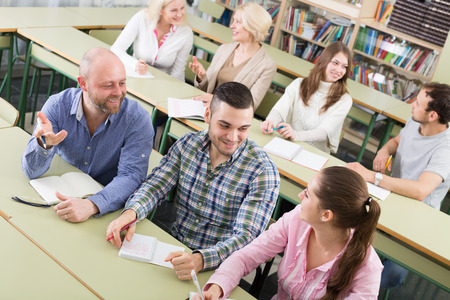attentive: Attentive adult students industriously writing down summary in the classroom Stock Photo