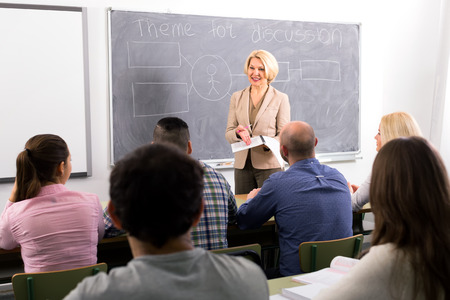 lecturing: Female professor standing in front of students and lecturing them
