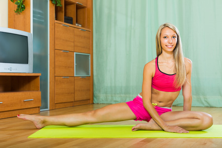 house trained: Positive young long-haired woman having pilates class indoor Stock Photo