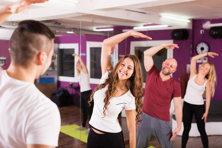 adult learners: Entrenador de la aptitud que muestra a los alumnos adultos felices nuevo ejercicio en la clase Foto de archivo