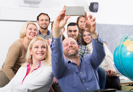 cohesive: Happy professionals and coach making group portrait in a school Stock Photo