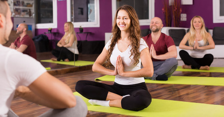 Positive smiling young adults having yoga class in sport club