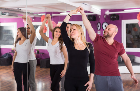 41937898: group of happy young people having dancing class indoors Stock Photo