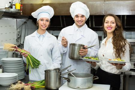 Personas de dos cocineros y camareros de sexo femenino en la cocina del restaurante. Enfoque selectivo