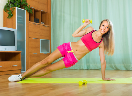 house trained: Young slender woman working out with dumbbells at home Stock Photo