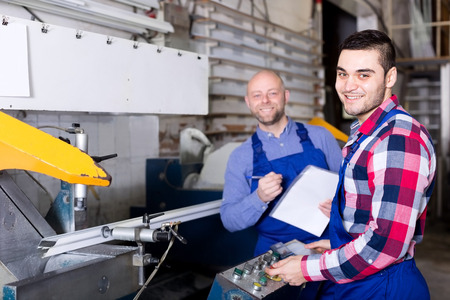 approving: Happy adult manager approving employee work at PVC windows factory Stock Photo