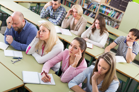 Bored unhappy adult students sitting at lesson in classroom