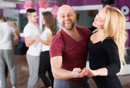 latin couple: Two happy smiling young couples having dancing class in club