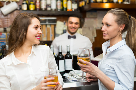 barmen: Two young beautiful girls flirting with handsome barman