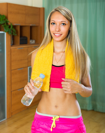 perspire: Happy sporty woman with towel holding plastic bottle of water