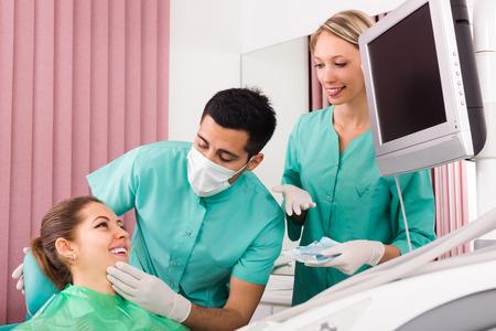 dentista: sonriente, alegre paciente y el dentista con su asistente durante el chequeo en la clínica