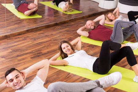 estudiantes adultos: Preparador f�sico feliz que muestra a adulto Estudiantes de nuevo ejercicio en la clase