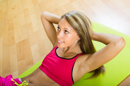 house trained: Cheerful active young woman working out  in gym Stock Photo