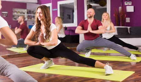 adult learners: Entrenador de la aptitud que muestra a adultos principiantes positivas nuevo ejercicio en la clase