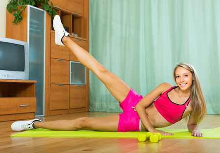 house trained: Positive happy young woman working out on exercise mat at home