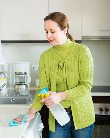 kitchen furniture: Smiling brunette woman cleaning furniture at domestic kitchen