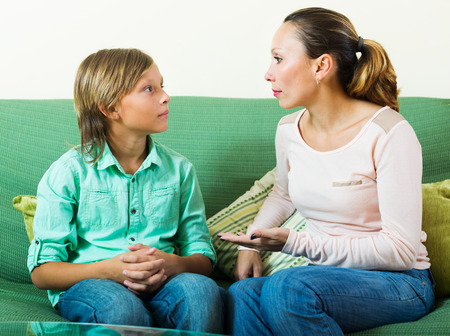 conversation: Mother with  teenager son having serious conversation in home