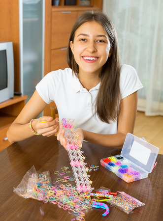 fancywork: Smiling girl making bracelets with elastic rainbow loom bands at the table