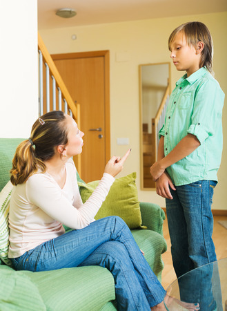 fracas: Mature mother scolding teenager son in living room at home Stock Photo