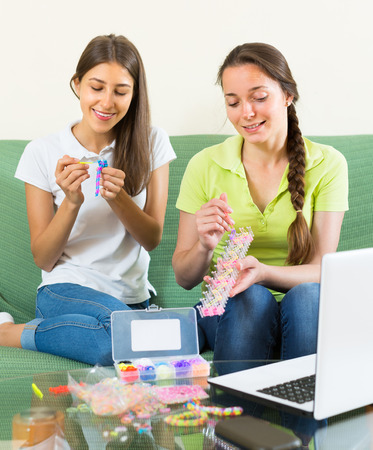 avocation: Two cheerful young sisters making decorative bracelet with elastics at home. selective focus