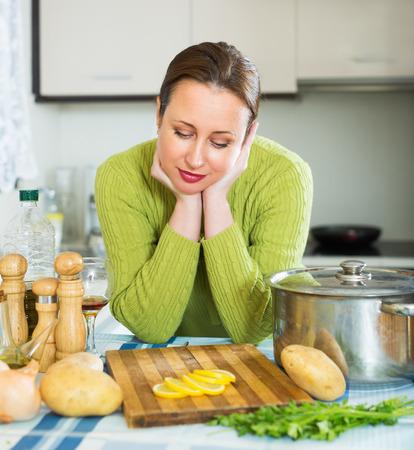 jornada de trabajo: Mujer joven agotada que tiene que hacer la cena despu�s de la jornada de trabajo