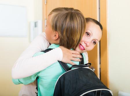 niños en la escuela: Madre positiva abrazando y dando conferencias hijo adolescente antes de que él va a la escuela