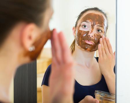 chocolate mask: Woman applying a facial mask at home
