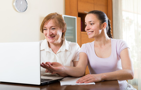 parsimony: american women with financial documents and laptop at table in home interior Stock Photo