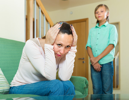 fracas: Mature mother sitting offended on sofa after quarrel with teenager son