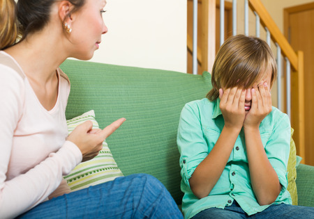 fracas: ordinary mother berating teenager son. Focus on boy