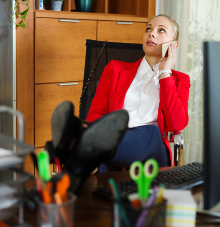 unbearable: Bored businesswoman speaking by mobile at office desk Stock Photo