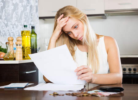 parsimony: Sad blonde woman calculating the family budget at home Stock Photo