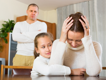 man and women: Family of three with daughter and angry man having conflict. Focus on girl