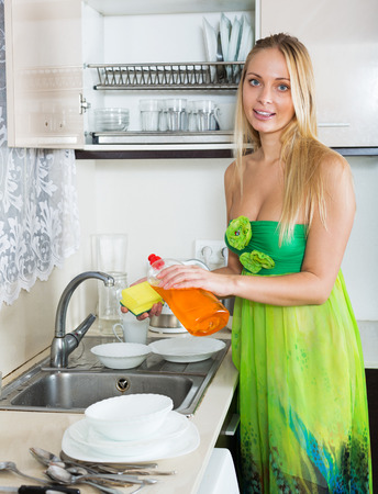 housewife in green washing dishes in  kitchen