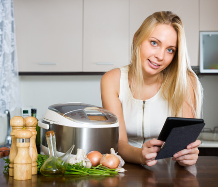 ereader: Blonde girl reading ereader while with new electric multicooker doing food at home Stock Photo