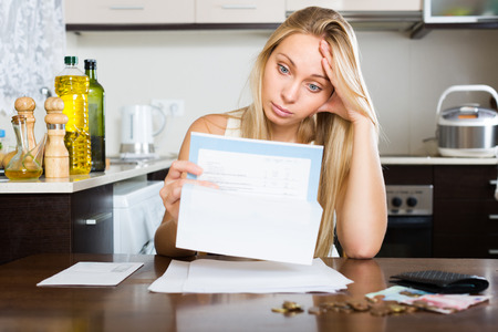 ruminate: Sad blonde young woman thinking about the financial issue at home Stock Photo