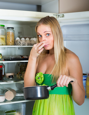 addle: Blonde young woman holding her nose because of bad smell near fridge at home Stock Photo