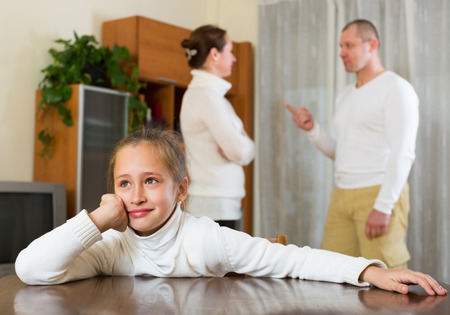 fracas: Parents and daughter quarrel at home. Focus on girl