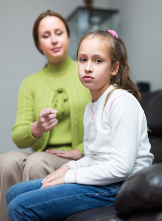 hysterics: angry mother berating  daughter at interior Stock Photo
