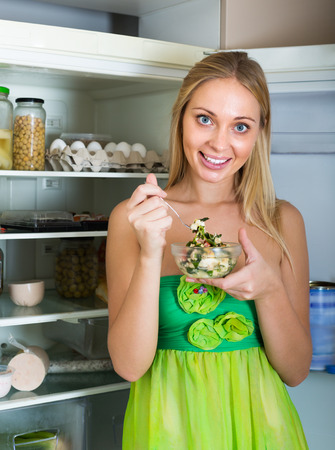 fridge: Hungry young woman near opening fridge eating salad