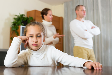 fracas: Sad daughter and parents having quarrel in the home. Focus on girl