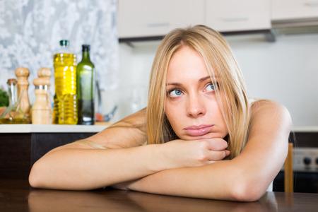fille pleure: Sad solitaire jeune femme blonde assise dans la cuisine � la maison